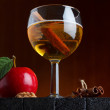Cider glass still life with apple and cinnamon stick on wooden table — Stock Photo