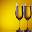 Stock Photo: Two champagne flute glasses on yellow background with copy space