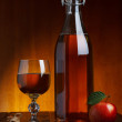 Glass and bottle of hot fresh autumn cider with apple and cinnamon stick on wooden table — Stock Photo