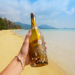 Bottle with a message in hand, on tropical island — Stock Photo