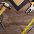 Stock Photo: Construction instruments on wooden table - sandpaper, pliers, measuring tape, hammer, nails