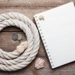Blank open notebook and sea rope with ancient coins, on wooden background — Stock Photo #27197323