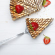 Slice of cheesecake with strawberry on cake lifter — Stock Photo
