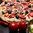Hot cooked pizza on wooden table with mushrooms, tomato and pepper still life — Stock fotografie