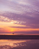 Sunset on sea during ebb with small fisherman boat on horizon — Stock Photo