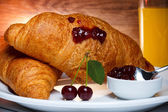 Fresh baked croissants with cherry jam and juice — Stock Photo