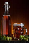 Pivo zátiší s čerstvým zeleným hop na rustikální dřevěný stůl — Stock fotografie