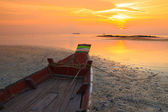 Small fishermans boat at sunset during ebb, focus on boat — Stock Photo