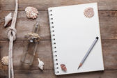 Weathered wooden table with blank notepad, pencil, rope and shells — Stock Photo
