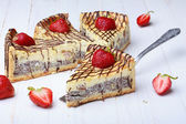 Slices of cheesecake with strawberry on wooden table, one on cake lifter — Stock Photo