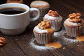 Cupcake with nuts and caramel on old wooden table — Stock Photo
