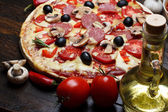 Hot cooked pizza on wooden table with mushrooms, tomato and pepper still life — Stock Photo