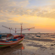 Stock Photo: Small wooden boat with light bulbs for night squid fishing on shore during ebb tide, Thailand