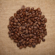 Coffee beans heap on sack — Stock Photo