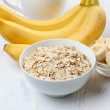 Bowl of oat flakes with sliced banana — Stock Photo