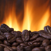 Coffee beans roasting with fire on background — Stock Photo