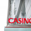 Red signboard of casino on old white building. — Stock Photo