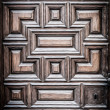 Old wooden door with carved geometric pattern. - Stock Photo