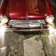 Red vintage car on road with working headlights. - Stock Photo