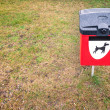Red dog waste bin on green lawn in park area. - Foto de Stock