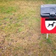 Red dog waste bin on green lawn in park area. - Foto Stock
