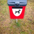 Red dog waste bin on green lawn in park area. - Stock Photo
