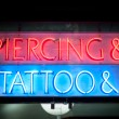 Neon signboard with Piercing & Tattoo at night. — Stock Photo