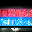 Neon signboard with Piercing & Tattoo at night. - Stock Photo