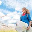Stock Photo: Young happy tourist woman with map in summer field.
