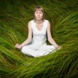 Blonde girl sitting on green grass and meditating. - Stock Photo