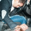 Young drunk driver sleeps in the car with bottle. - Stock Photo