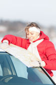 Beautiful woman near car holding map in winter. — Stock Photo