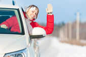 Happy beautiful woman travels by car in winter. — Stock Photo