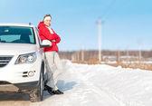 Vacker kvinna står nära vit bil på vintern. — Stockfoto