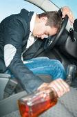 Jeune conducteur ivre dort dans la voiture avec bouteille. — Photo