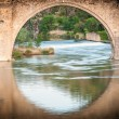 Bridge reflects in river of Toledo, Spain, Europe. - Stock Photo