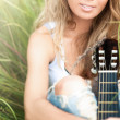 Beautiful woman with guitar sitting on grass. — Stock Photo