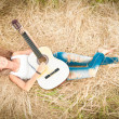Happy girl with guitar lying on grass in meadow. - Stock Photo
