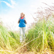 Young girl walking in meadow with backpack on. - Stock Photo