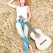 Stock Photo: Happy girl with guitar lying on grass in meadow.