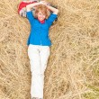 Laughing woman lying down on grass in meadow. - Stock Photo