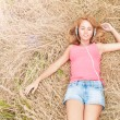 Young pretty woman in headphones on hay. — Stock Photo