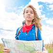 Young happy tourist woman with map in summer field. - Stock Photo
