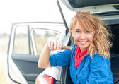 Happy girl sitting in car and holding chocolate. — Stockfoto