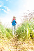Young girl walking in meadow with backpack on. — Foto Stock