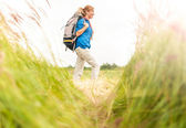 Young girl walking in meadow with backpack on. — Stockfoto
