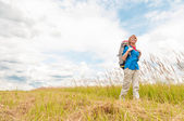 Young girl walking in meadow with backpack on. — Stock fotografie