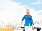 Tourist woman in front of car in summer field. — Stock fotografie