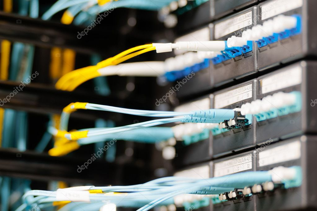 Internet service provider equipment. Focus on panel with optic cables connected to panel in datacenter. Network server room. Modern technology. Yellow and blue cables contrast with dark background.  Stock Photo #14753649