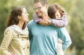 Familia feliz de tres divirtiendo al aire libre. — Foto de Stock